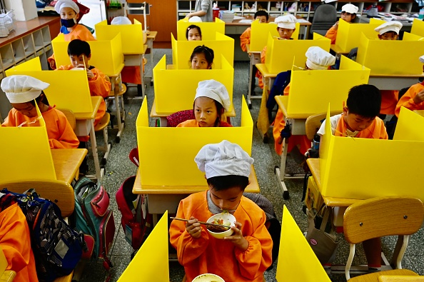 TOPSHOT - Students eat their lunch on desks with plastic partitions as a preventive measure to curb the spread of the COVID-19 coronavirus at Dajia Elementary School in Taipei on April 29, 2020. (Photo by Sam Yeh / AFP) (Photo by SAM YEH/AFP via Getty Images)